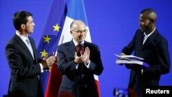 Le Premier ministre français Manuel Valls et ministre de l'Intérieur Bernard Cazeneuve applaudissent comme Lassana Bathily, 24, détient ses papiers de citoyenneté lors d'une cérémonie au ministère de l'Intérieur à Paris, 20 janvier 2015.