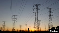 FILE - A man walks past electricity pylons as he returns from work in Soweto, outside Johannesburg.