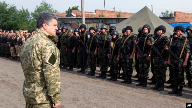 FILE - In this photo taken June 20, 2014, in Izyum, near Slovyansk, eastern Ukraine, Ukrainian President Petro Poroshenko visits troops.