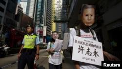 Seorang demonstran pro-demokrasi (kanan) memakai masker tahanan politik China Xu Zhiyong, yang dituduh melanggar ketertiban umum, dalam sebuah protes di Hong Kong. (Foto: Dok)