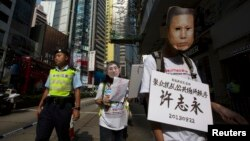 A pro-democracy protester, wearing a mask depicting a Chinese political prisoner calls for the release of political prisoners in Hong Kong, Oct. 1, 2013.