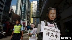 A pro-democracy protester, wearing a mask depicting a Chinese political prisoner, carries a placard, with the prisoner's name and his charges, during a protest calling for the release of political prisoners in Hong Kong, Oct. 1, 2013.