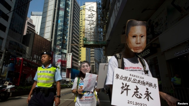 FILE - A pro-democracy protester, wearing a mask depicting a Chinese political prisoner, carries a placard, with the prisoner's name and his charges, during a protest calling for the release of political prisoners in Hong Kong, Oct. 1, 2013.