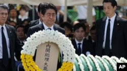Japanese Prime Minister Shinzo Abe holds a wreath during a ceremony to mark the 70th anniversary of the Nagasaki atomic bombing in Nagasaki, southern Japan, Aug. 9, 2015.