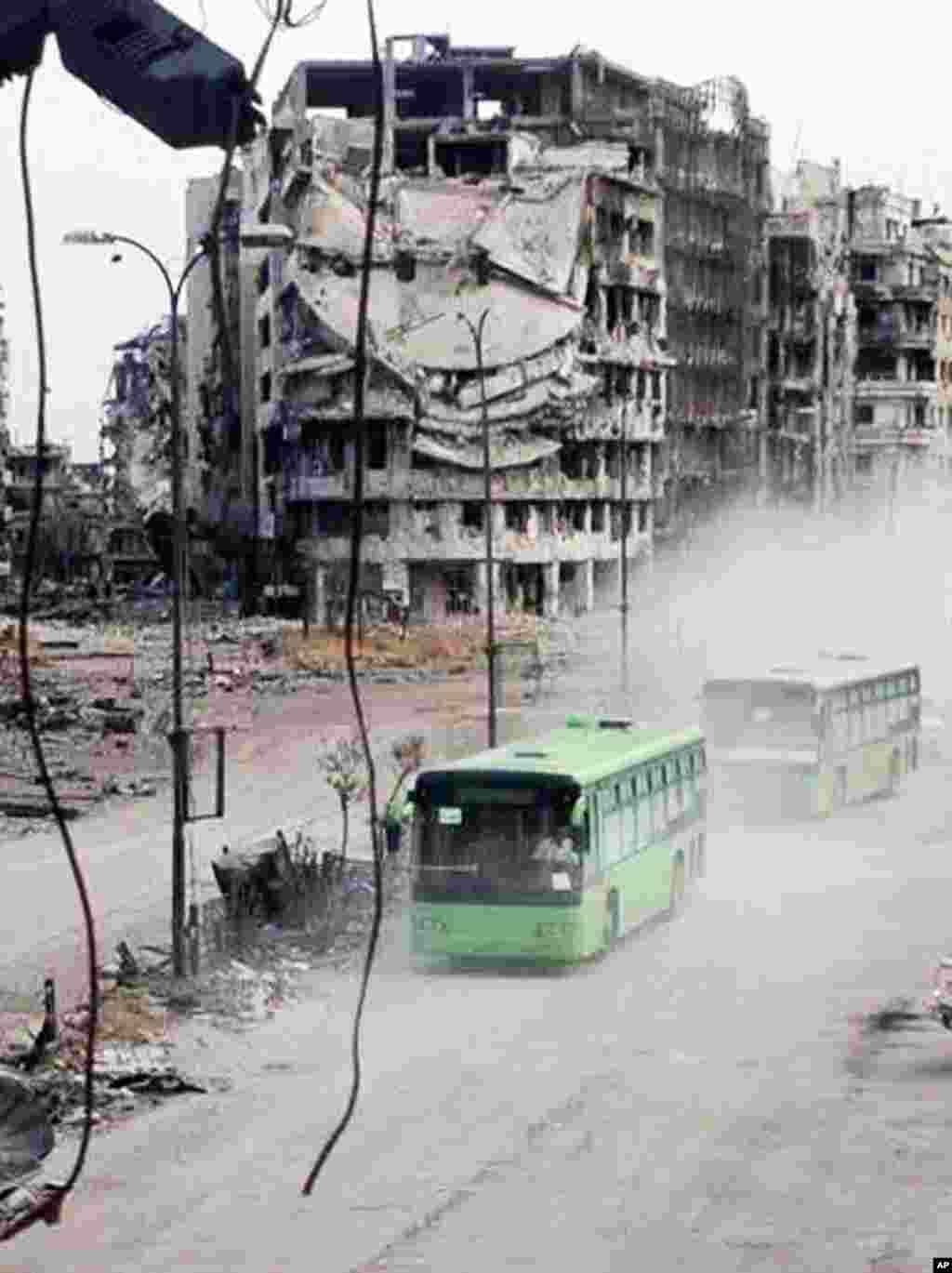 Bus-bus yang membawa para pejuang yang tergabung dalam Tentara Pembebasan Suriah, terlihat tengah meninggalkan kota Homs, 7 Mei 2014. (Foto: AP/ Komite Koordinasi Wilayah Khalidiya di Homs).