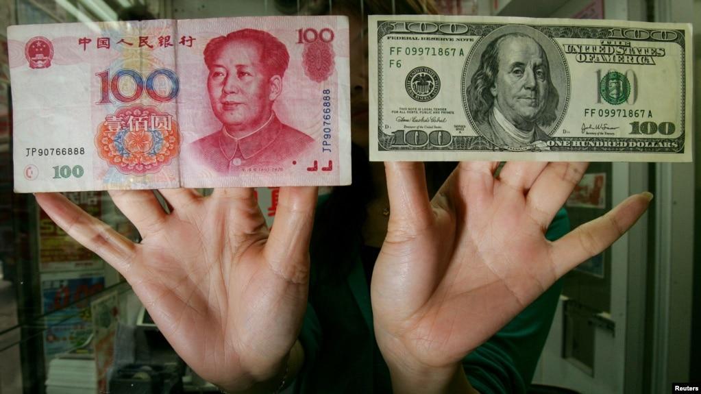 香港一家貨幣兌換店裡的僱員展示人民幣和美元百元鈔票