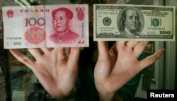 FILE - An exchange store staff shows a Chinese RMB$100 banknote (L) and a US$100 banknote in Hong Kong, May 16, 2006.