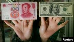 香港一家货币兑换店里的雇员展示人民币和美元百元钞票