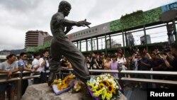 Para penggemar legenda kung fu Bruce Lee menghiasi patungnya di pelabuhan Victoria, Hong Kong dengan karangan bunga untuk menghormati 40 tahun kematiannya (20/7).