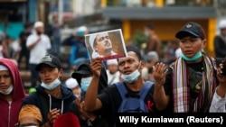 Seorang demonstran mengacungkan gambar Rizieq Shihab yang baru saja divonis karena melanggar pembatasan terkait COVID-19, Kamis, 24 Juni 2021. (Foto: Willy Kurniawan/Reuters)