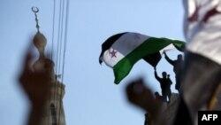 Фотография была сделана в пятницу в городе на севере Сирии. Неизвестный размахивает флагом сирийской оппозиции.