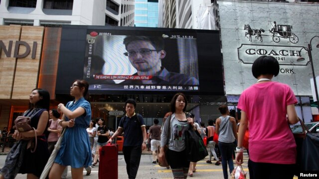 People cross a street in front of a monitor showing file footage of Edward Snowden, a former contractor for the U.S. National Security Agency (NSA), with a news tag (L) saying he has left Hong Kong, in Hong Kong June 23, 2013.