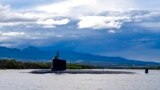 FILE - In this photo provided by U.S. Navy, a submarine departs Joint Base Pearl Harbor-Hickam, Sept. 1, 2021.