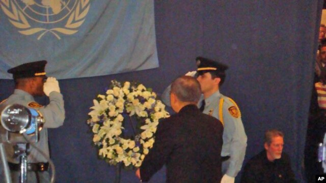 Secretary-General Ban Ki-moon faces flag that flew over UN mission in Haiti at memorial service in New York, 19 Jan 2010