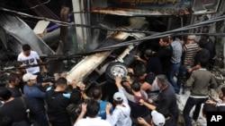 叙利亚官方通讯社发表的图片显示,2012年11月5日首都大马士革发生一次爆炸事件之后,叙利亚人民将一部汽车推到。