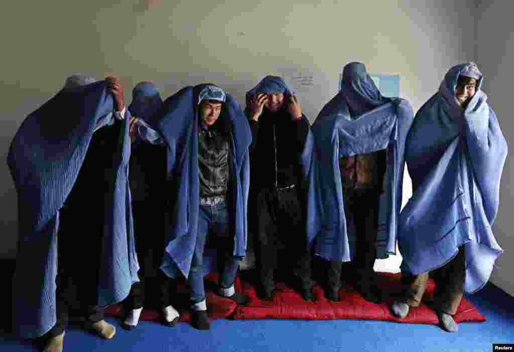 Male Afghan women's rights activist wear burqas to show their solidarity to Afghan women ahead of International Women's Day in Kabul.