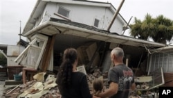 Maree, left, daughter Jasmine, center, and Norm Butcher take a look at their destroyed home in Christchurch, New Zealand , February 26, 2011