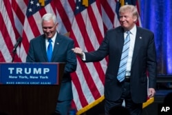 Republican presidential candidate Donald Trump, right, introduces Gov. Mike Pence, R-Ind., during a campaign event to announce Pence as the vice presidential running mate on, Saturday, July 16, 2016, in New York.