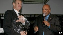 Scott Neeson , left, the Executive Director of The Cambodian Children's Fund, a safe house for Cambodia's orphaned and abused children accepts the inaugural Q prize award from Quincy Jones, right, in New York on Wednesday, Jan. 24, 2007.