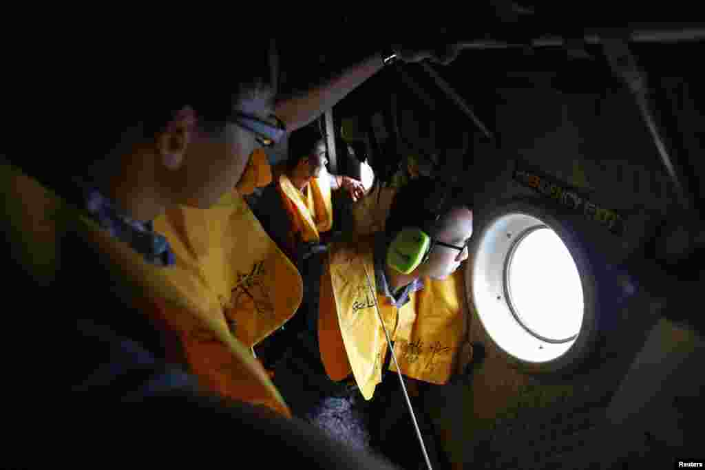 Republic of Singapore Air Force personnel survey the waters during a search and locate operation for the missing AirAsia flight QZ8501 plane at an undisclosed search area, Dec. 30, 2014.