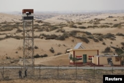 An Egyptian policeman gestures from an observation tower is seen from the Israeli side of the border with Egypt's Sinai peninsula, in Israel's Negev Desert Feb. 10, 2016.