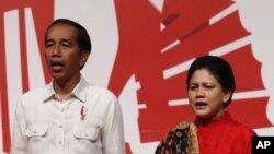 """Presiden Joko Widodo dan ibu negara, Iriana, menyanyikan lagu """"Indonesia Raya"""" dalam pertemuan dengan warga Indonesia di Hong Kong, 30 April 2017. (AP Photo/Vincent Yu)"""