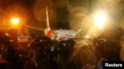 Petugas berusaha mencari korban selamat setelah pesawat Air India Express jatuh hari Jumat (7/8).