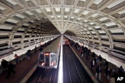 FILE - Metro trains arrive in the Gallery Place-Chinatown Metro Station in Washington, March 15, 2016.