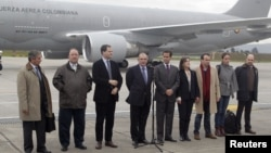 Colombia's government head of negotiators Humberto de la Calle (C) speaks next to delegation members prior to boarding a plane to Oslo, at a military airport in Bogota October 16, 2012. Colombia's government and Marxist rebels will start peace talks as pl