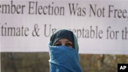 A former legislator, her face covered presumably to obscure her identity, marches during the post-election protest in Kabul, 7 November 2010