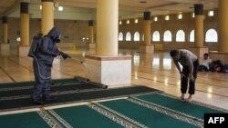 ایک مسجد میں کرونا وائرس کے خلاف ادویات کا چھڑکائو کیا جا رہا ہے۔
