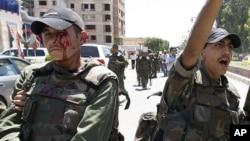 Một binh sĩ Syria bị thương đi cạnh đồng đội sau khi một quả bom phát nổ làm rung chuyển các quân xa tháp tùng một đoàn xe chở các giám sát viên Liên hiệp quốc tại Syria, ngày 9/5/2012