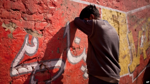 A drug addict leans on a wall after injecting himself with a dose of heroin on a street in Rawalpindi, Pakistan, Feb. 14, 2012.