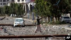 Phiến quân Houthi đi trên con đường đầy những mảnh vỡ sau một cuộc không kích của Ả Rập Xê Út tại thủ đô Yemen.