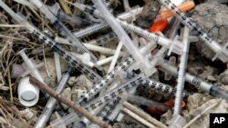 FILE - In this May 22, 2008 file photo, used syringes and needles are piled on the ground under an underpass on the west side of San Antonio where drug addicts shoot up.