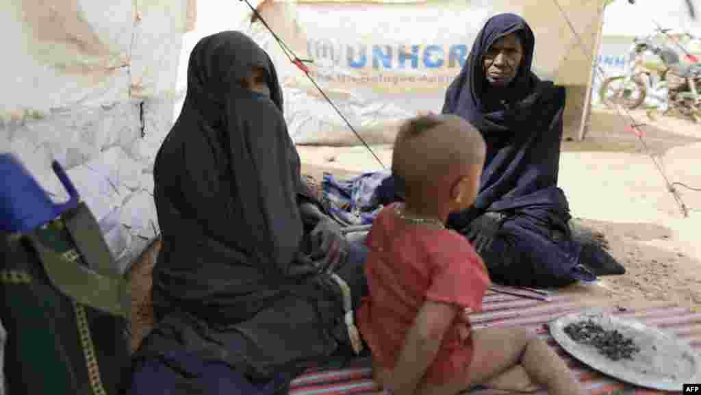 马里女难民和一个小孩2013年1月24日坐在靠近马里边界附近联合国难民署搭设的帐篷旁边