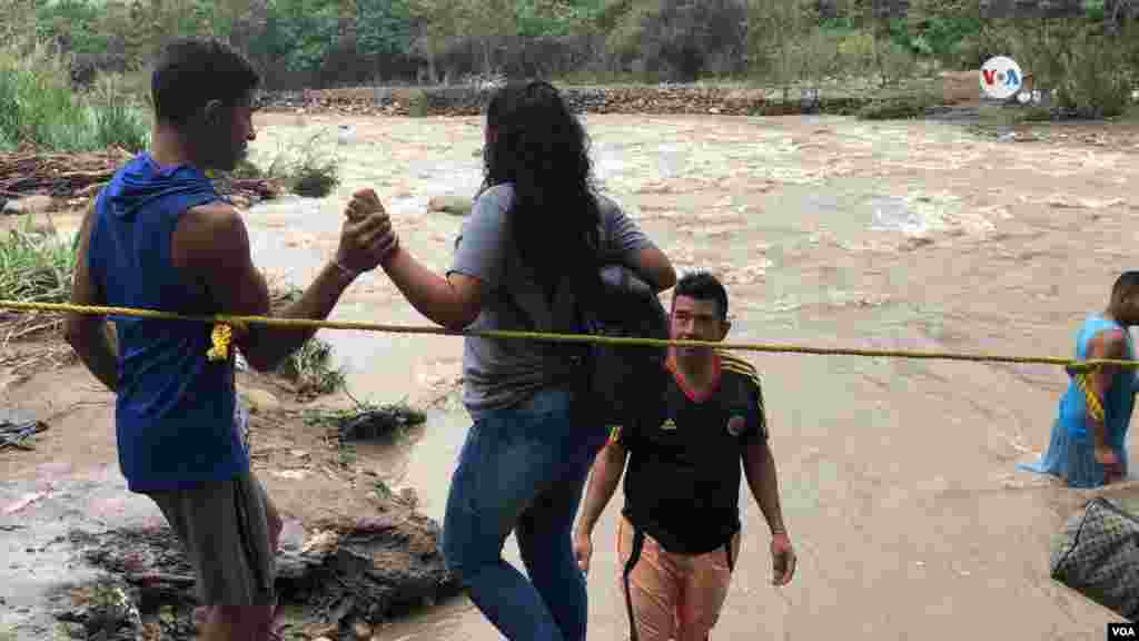 Venezolanos intentan cruzar el río Táchira, sin importar los peligros.