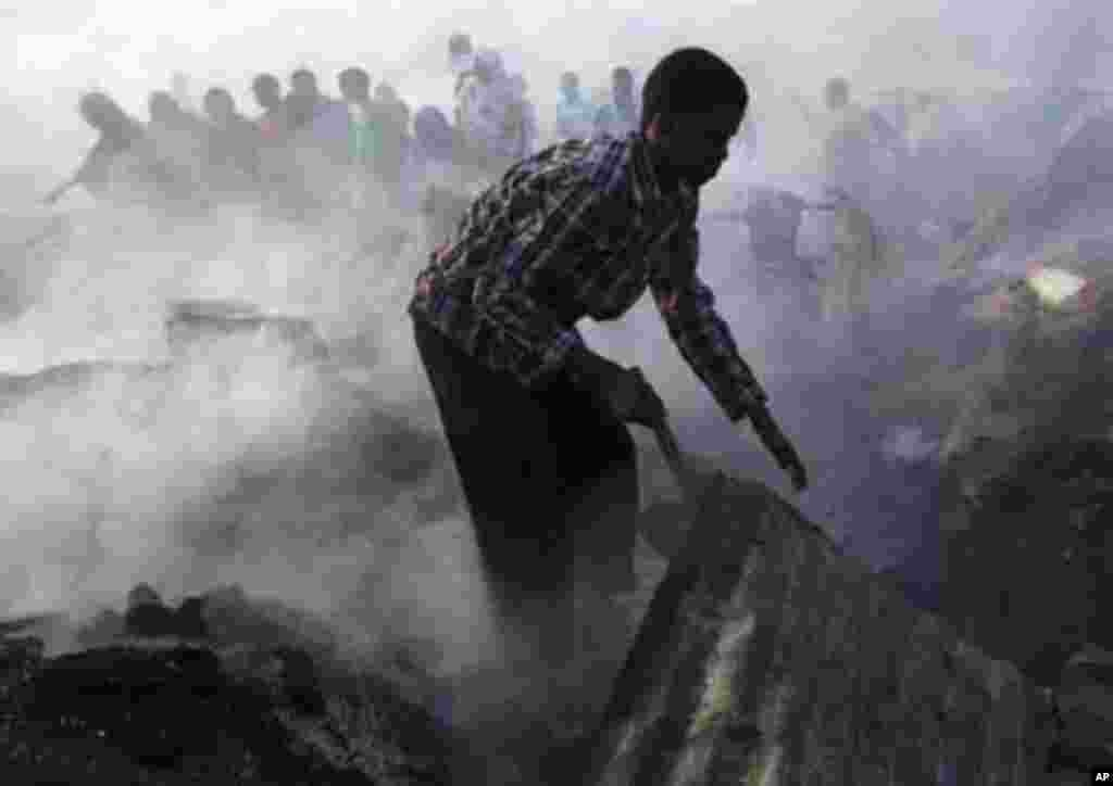 A man stands near debris at the scene of a fire that razed an entire market in Hamaerweyne district south of capital Mogadishu January 26, 2012. REUTERS/Feisal Omar (SOMALIA - Tags: DISASTER ENVIRONMENT BUSINESS)