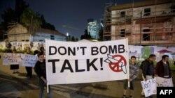 Израильтяне держат баннер во время акции протеста против нападения на Иран