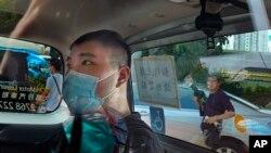 香港首位被控涉嫌違反國安法的男子唐英傑坐著輪椅由警車押解至法院應訊(2020年7月6日)