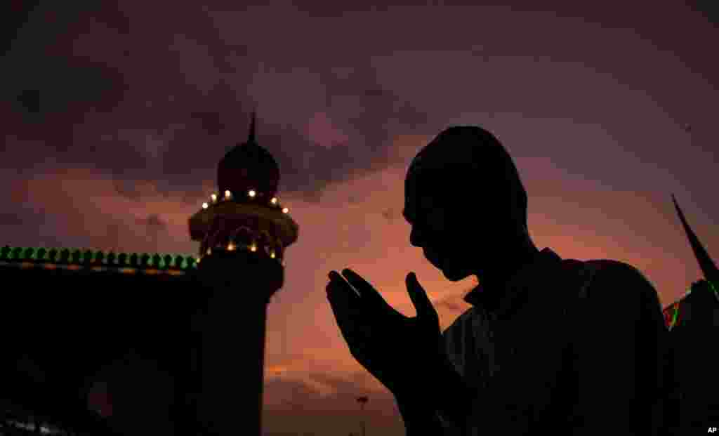A Muslim offers prayers before breaking his fast on the first day of the holy fasting month of Ramadan at Mecca Masjid in Hyderabad, India.