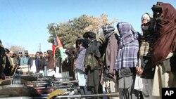 1月16日在喀布爾西部加茲尼,一名前塔利班激進分子(中)參加他加入阿富汗政府的 儀式