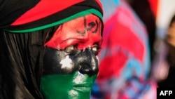 """Bingazi'de yüzünü isyancıların kullandığı krallık döneminin bayrağının renklerine boyayan bir Libyalı kadın alnına da Kaddafi'ye ithafen """"Çek git"""" diye yazmış"""