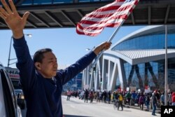 """Hailun Song waves a U.S. flag and cheers marchers as a """"Stop Asian hate"""" rally in downtown Atlanta passes by, March 20, 2021."""