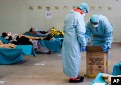 Paramedics carry an hazardous medical waste box as patients lie on camping beds, in one of the emergency structures that were set up to ease procedures at the Brescia hospital, northern Italy, March 12, 2020.