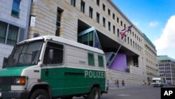A police vehicle is parked in front of the British Embassy in Berlin, Germany, Aug. 11, 2021. German prosecutors say they have detained a British citizen who is accused of spying for Russia while working at the embassy.