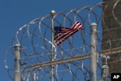 FILE - A US flag flies inside the razor wire of the Camp VI detention facility in Guantanamo Bay Naval Base, Cuba, in April 2019.