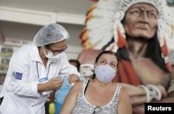 Una mujer recibe una dosis de la vacuna contra la enfermedad del coronavirus CoronaVac (COVID-19) de Sinovac en Cacique de Ramos, uno de los sectores de carnaval más tradicionales de Río de Janeiro, Brasil, el 8 de abril de 2021.