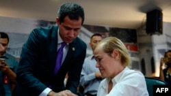 Venezuelan opposition leader and self-proclaimed acting president Juan Guaido (L) comforts oncological patient Mildred Valera during a special consultation commission meeting at the National Assembly building in Caracas on August 27, 2019. / AFP /…