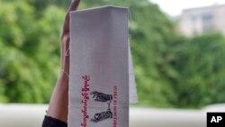 ဖမ္းဆီးခံ သတင္းေထာက္တဦးလြတ္ေျမာက္ေရး ဆႏၵျပ ပိုစတာတခု (ဓာတ္ပံု- AP Photo/Thein Zaw)